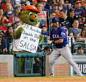 P Arencibia of the Texas Rangers is harassed by Houston Astros mascot Orbit as he waits on deck at Minute Maid Park on August 10 2014 in Houston Texas