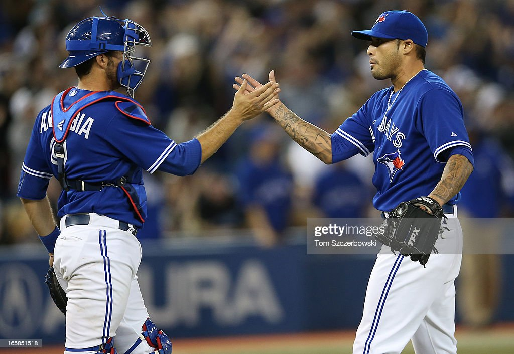 J.P. Arencibia #9 of the Toronto Blue Jays celebrates with Sergio Santos #21 during MLB game action after defeating the Boston Red Sox on April 6, 2013 at Rogers Centre in Toronto, Ontario, Canada.