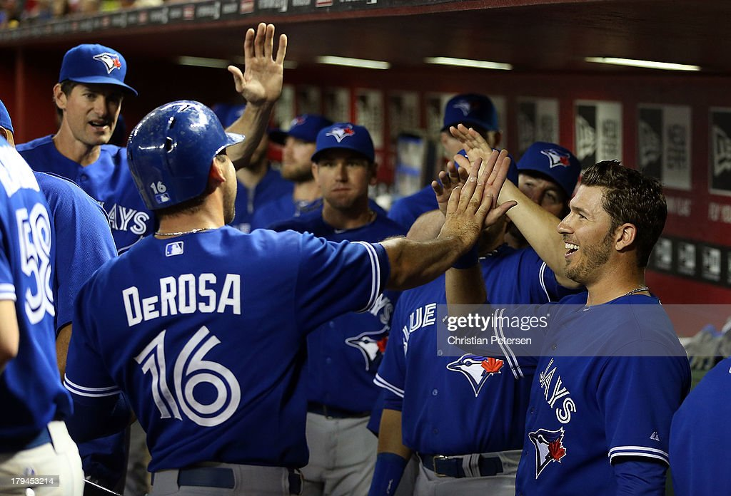 <a gi-track='captionPersonalityLinkClicked' href=/galleries/search?phrase=J.P.+Arencibia&family=editorial&specificpeople=4959430 ng-click='$event.stopPropagation()'>J.P. Arencibia</a> #9 (R) of the Toronto Blue Jays high-fives <a gi-track='captionPersonalityLinkClicked' href=/galleries/search?phrase=Mark+DeRosa&family=editorial&specificpeople=228401 ng-click='$event.stopPropagation()'>Mark DeRosa</a> #16 after he scored a fifth inning run against the Arizona Diamondbacks during the interleague MLB game at Chase Field on September 3, 2013 in Phoenix, Arizona.
