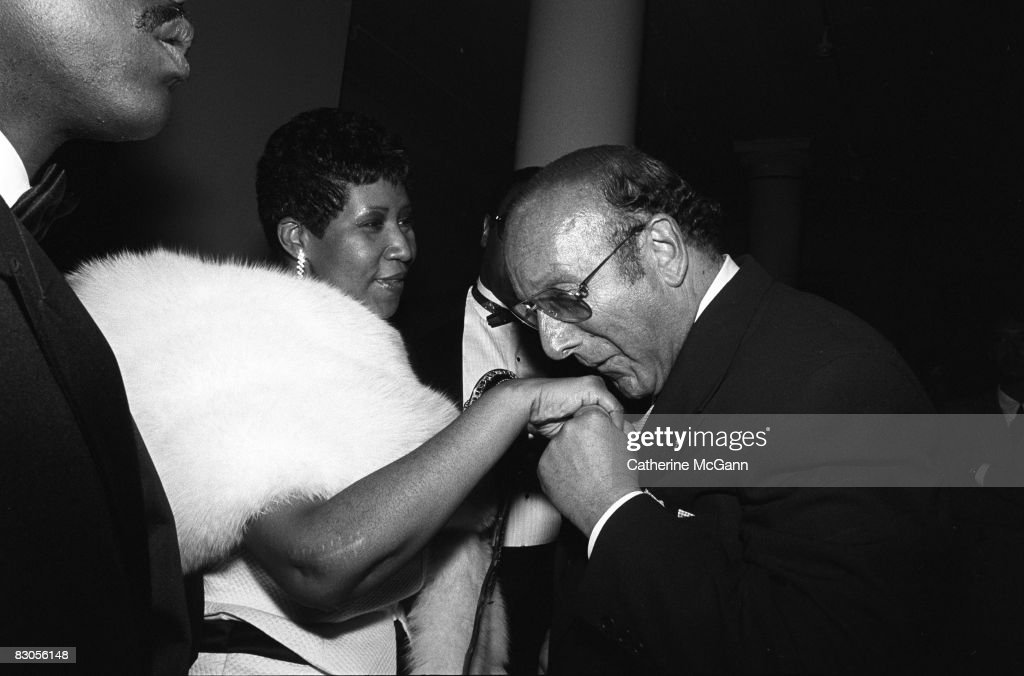 Aretha Franklin, left, extends her hand to be kissed by American record producer and music industry executive Clive Davis, right, at a party in July 1989 in New York City, New York.