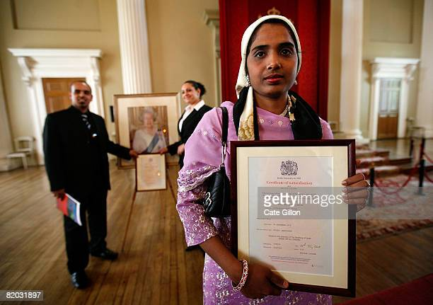 Arfa Khatun Chowdury from Bangladesh holds her certificate of naturalisation after becoming a British citizen at a Citizenship Ceremony for forty...