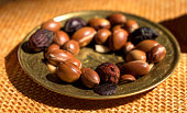 Argan nuts seeds on a plate - Argan is useful as antioxidant for healing redness inflammations skin stretch marks