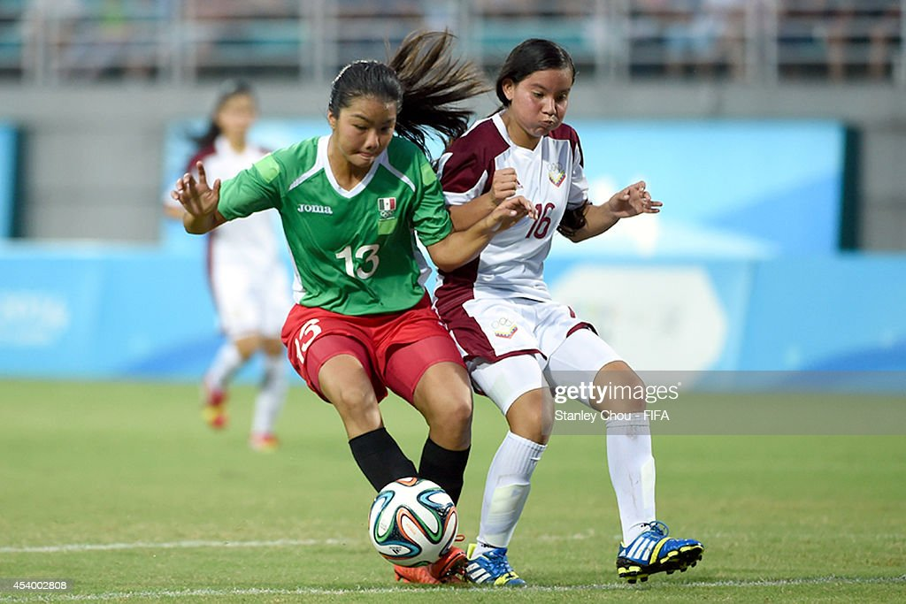 Argelis Campos of Venezuela competes with Akemi Yokoyama of Mexico during the 2014 FIFA Girls Summer Youth Olympic Football Tournament Semi Final match between Venezuela and Mexico at Wutaishan Stadium on August 23, 2014 in Nanjing, China.