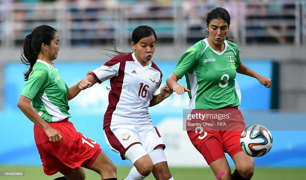Argelis Campos of Venezuela competes with Maria Acedo and Akemi Yokoyama of Mexico during the 2014 FIFA Girls Summer Youth Olympic Football Tournament Semi Final match between Venezuela and Mexico at Wutaishan Stadium on August 23, 2014 in Nanjing, China.