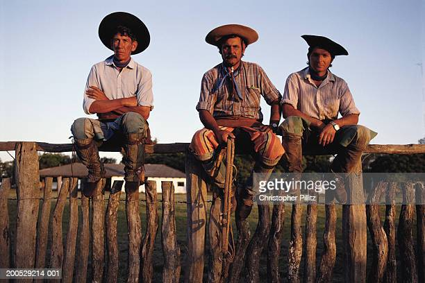 Argentina, Buenos Aires, three gauchos sitting on fence at ranch