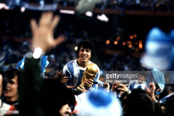 Argentina captain Daniel Passarella clings on to the World Cup as he is carried shoulderhigh by celebrating Argentina fans after the match