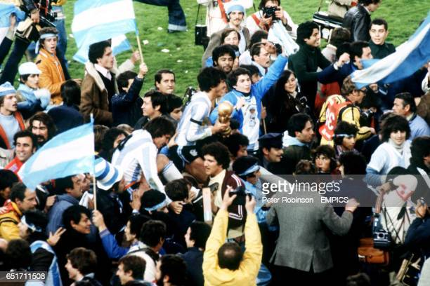 Argentina captain Daniel Passarella clutching the World Cup tightly is carried shoulderhigh by celebrating Argentina fans after the match