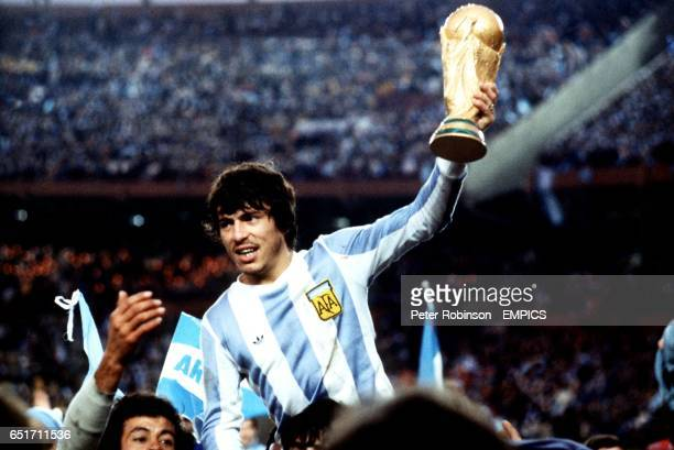 Argentina captain Daniel Passarella shows off the World Cup to the celebrating Argentina fans as they mob the players