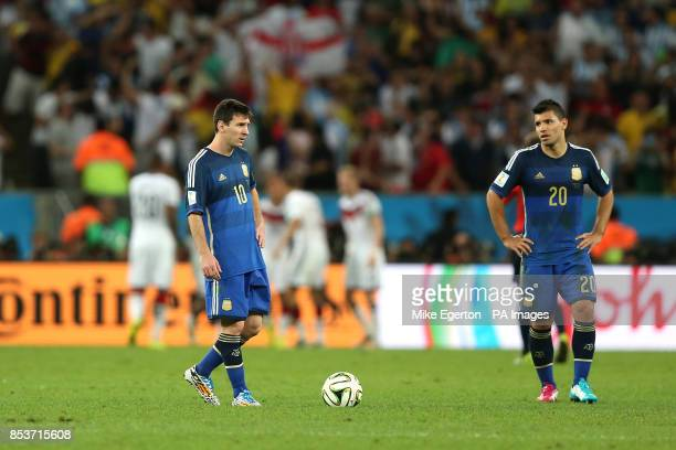 Argentina captain Lionel Messi and teammate Sergio Aguero stand dejected as Germany players celebrate scoring the winning goal