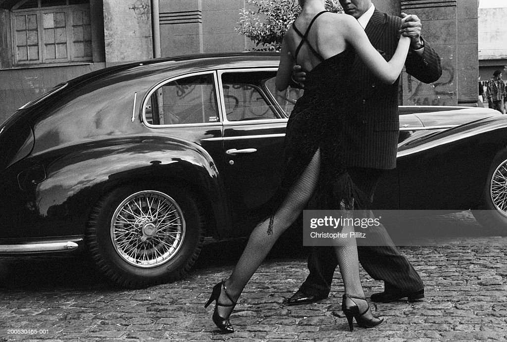 Argentina, couple dancing tango by car in street (B&W) : Stock Photo