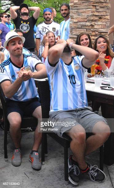 Argentina fans Damiano Alloggia and Omar Ashraf react during the Germany vs Argentina World Cup finals viewing party at the Red Fox English Pub and...