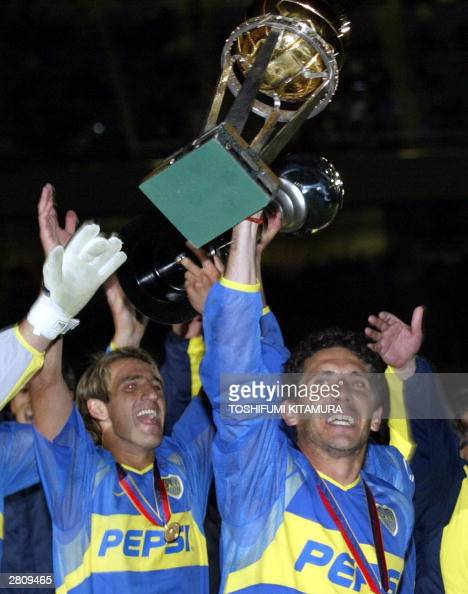 Argentina football club Boca Juniors' captain Diego Cagna holds up the InterContinental cup as Alfredo Raul Cascini carries the Toyota Cup after...