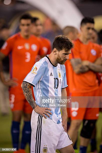 Argentina forward and captain Lionel Messi waits to take his 2nd place medal while Chile defender Enzo Roco and Chile midfielder Pablo Hernandez look...