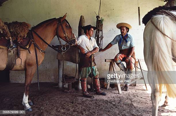 Argentina, gauchos with horses in stable