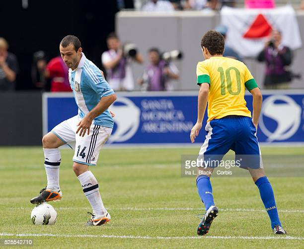 Argentina National Team player Javier Mascherano drives forward against Brazil player Oscar during the Clash of the Titans match between Argentina...