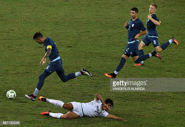 Argentina player Victor Cuesta vies for the ball with Algeria player Baghdad Bounedjah during the Rio 2016 Olympic Games men's First Round Group D...