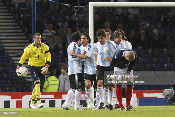 Argentina players celebrate with goalscorer Maximiliano Rodriguez after scoring their first goal of the game as Scotland goalkeeper Allan McGregor...