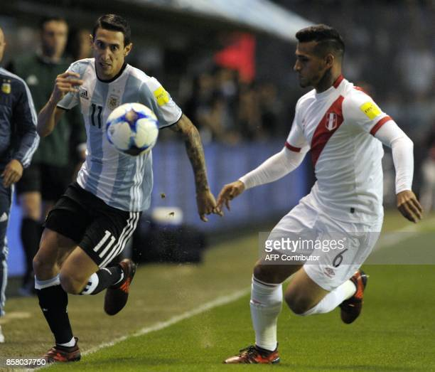 Argentina's Angel Di Maria and Peru's Miguel Trauco run for the ball during their 2018 World Cup qualifier football match in Buenos Aires on October...