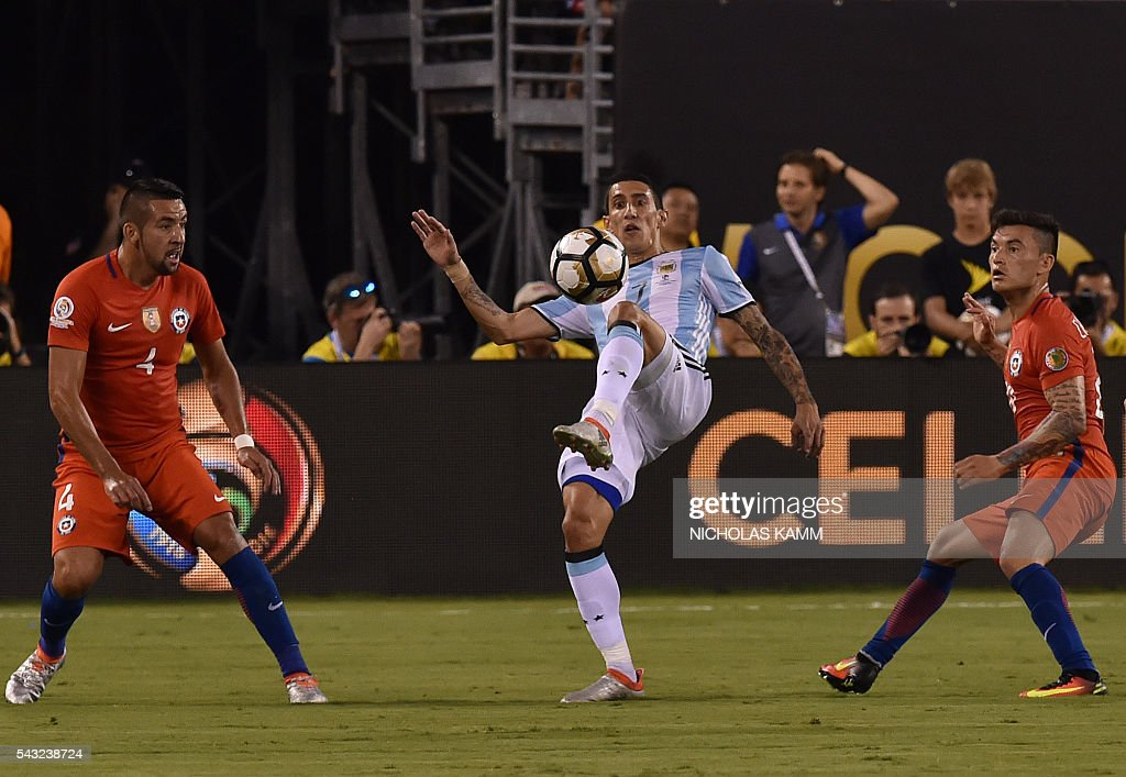 Argentina's Angel Di Maria (C) kicks the ball eyed by Chile's Mauricio Isla (L) and Chile's Charles Aranguiz during the Copa America Centenario final in East Rutherford, New Jersey, United States, on June 26, 2016. / AFP / Nicholas KAMM