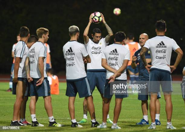 CORRECTION Argentina's Angel Fabian Dimaria and teammates listen to coach Jorge Sampaoli's briefing before the start of a training session at Bishan...