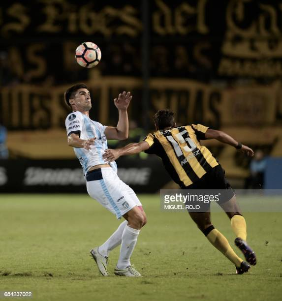 Argentina's Atletico Tucuman Fernando Evangelista vies for the ball with Uruguay's Penarol Hernan Petryk during their Libertadores Cup football match...