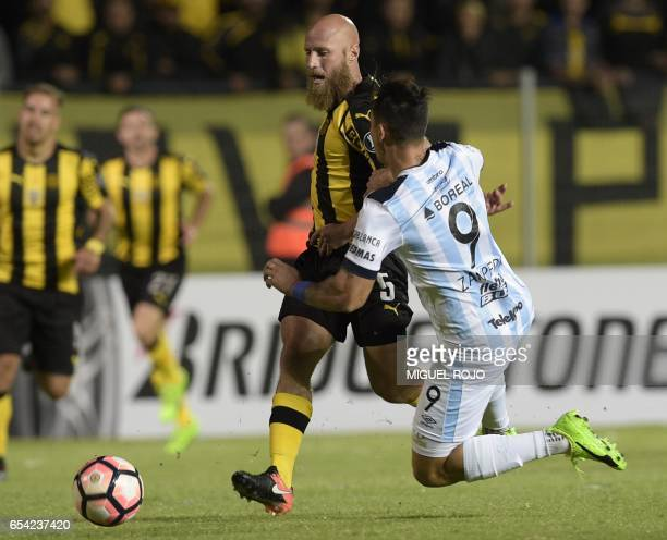 Argentina's Atletico Tucuman Fernando Zampedri vies for the ball with Uruguay's Penarol Marcel Novick during their Libertadores Cup football match at...