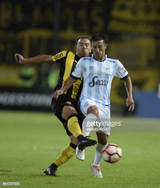 Argentina's Atletico Tucuman Guillermo Acosta vies for the ball with Uruguay's Penarol Junior Arias during their Libertadores Cup football match at...