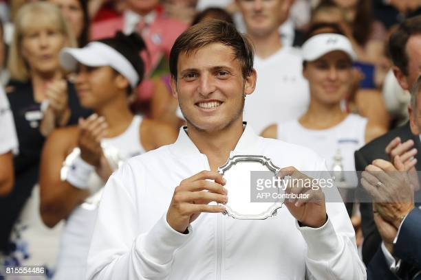 Argentina's Axel Geller holds his runner's up trophy after losing his boys' singles final match against Spain's Alejandro Davidovich Fokina on the...