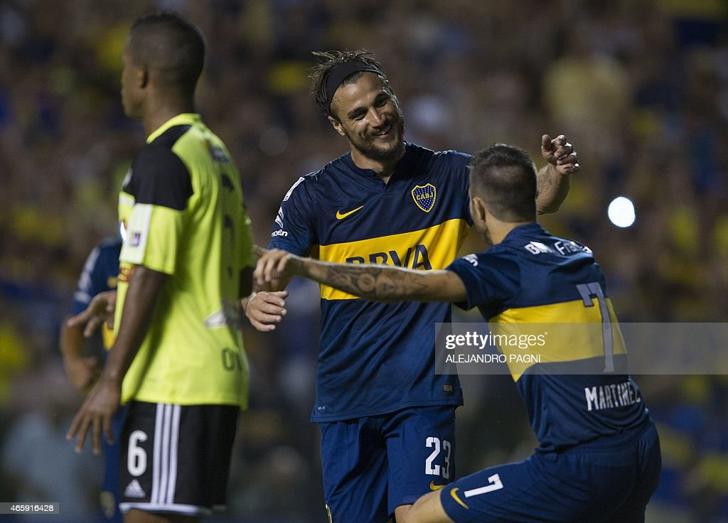 Argentina's Boca Juniors' forward Daniel Osvaldo (C) celebrates with forward Juan Manuel Martinez (R) after scoring the team's fourth goal against Venezuela's Zamora during their Copa Libertadores 2015 group 5 football match at La Bombonera stadium in Buenos Aires, Argentina, on March 11, 2015.