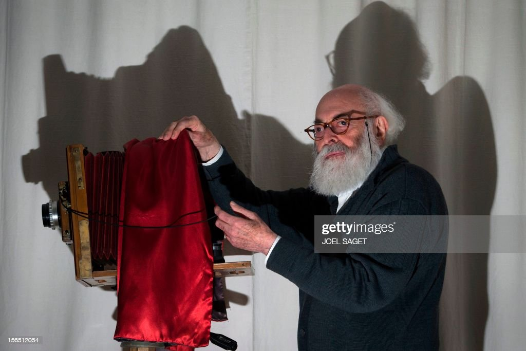 Argentina's born and French photographer, Adolfo Kaminsky poses in front of 'Lorillon' view camera on November 16, 2012 at his home in Paris. Born in a Jewish family from Russia, Kaminsky is a former French Resistance, who forged identity documents for the National Liberation Front and French draft dodgers during the Algerian War. AFP PHOTO /JOEL SAGET
