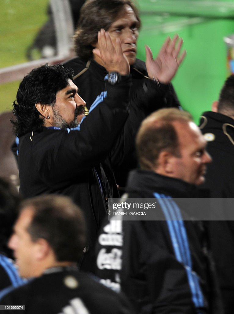 Argentina's coach Diego Maradona, surrounded by assitants, applauds supporters at the end of a team training session at the University's High Performance Centre in Pretoria on June 6, 2010 ahead of the start of the 2010 football World Cup.
