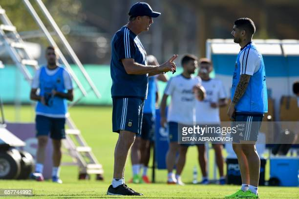 Argentina's coach Edgardo Bauza speaks with midfielder Ever Banega during in a training session in Ezeiza Buenos Aires on March 25 2017 ahead of a...