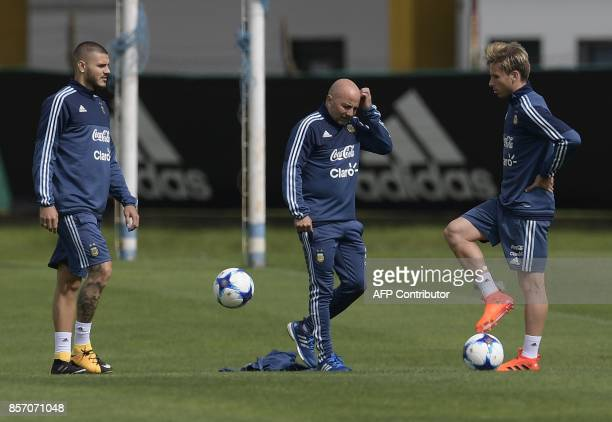 Argentina's coach Jorge Sampaoli scratch his head next to forward Mauro Icardi and midfielder Lucas Biglia during a training session in Ezeiza Buenos...