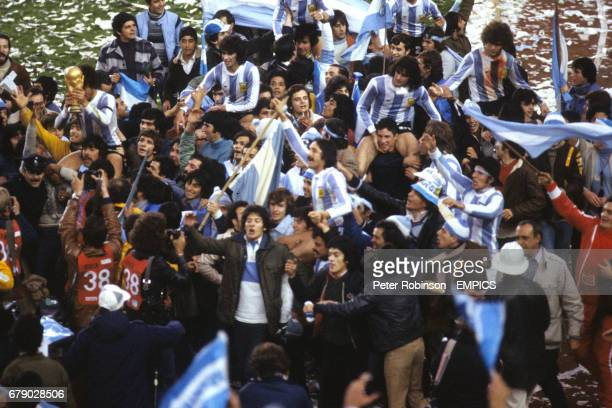 Argentina's Daniel Passarella holds the World Cup as fans invade the pitch and hoist players on their shoulders