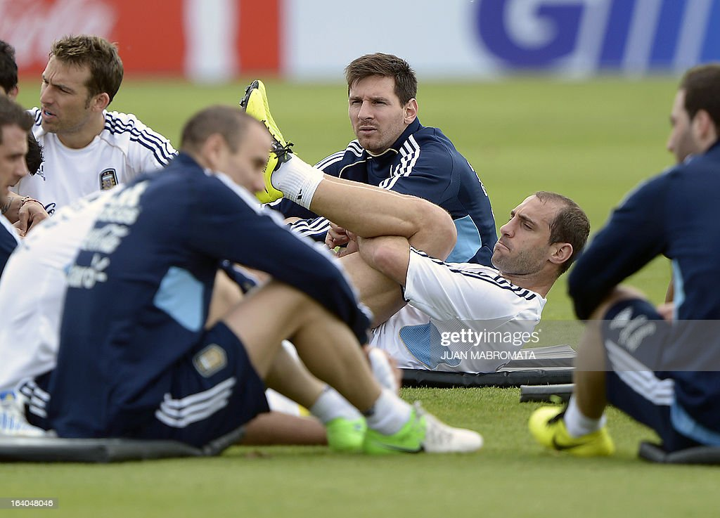 Argentina's defender Pablo Zabaleta (2-R) stretches next to Lionel Messi (C) and other teammates during a training session in Ezeiza, Buenos Aires on March 19, 2013 ahead of the Brazil 2014 FIFA World Cup South American qualifier football match against Venezuela on March 22. AFP PHOTO / Juan Mabromata