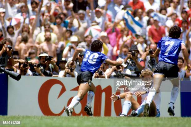 Argentina's Diego Maradona celebrates scoring his and his team's second goal as teammate Jorge Burruchaga gives chase and England's Terry Butcher...
