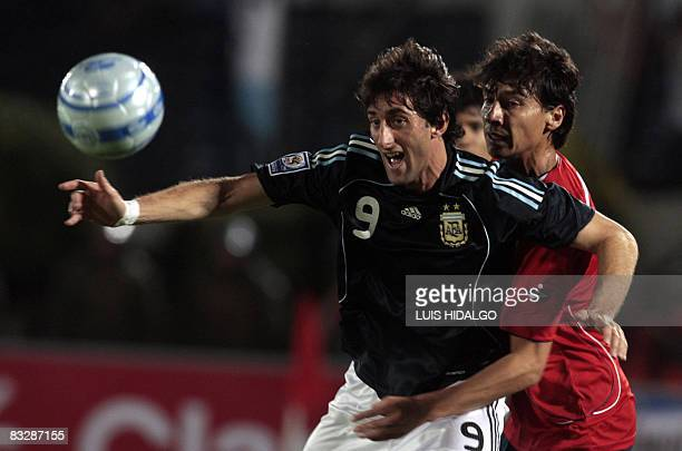 Argentina's Diego Milito vies for the ball with Chile's Pablo Contreras during their FIFA World Cup South Africa2010 qualifier match at the National...