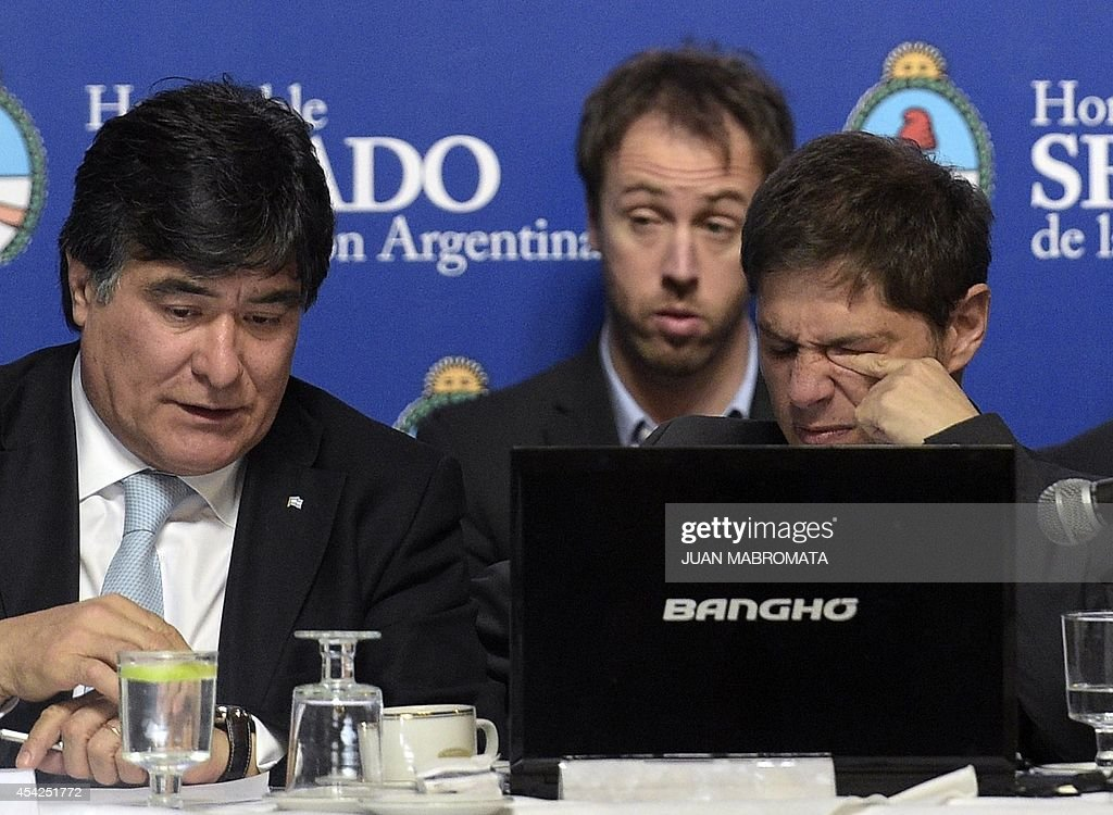 Argentina's Economy Minister Axel Kicillof (R) gestures next to Argentina's General Secretary of the Presidency Carlos Zannini during their appear in the Congress about the bill to pay the debt at the Banco Nacion, Buenos Aires on August 27, 2014.