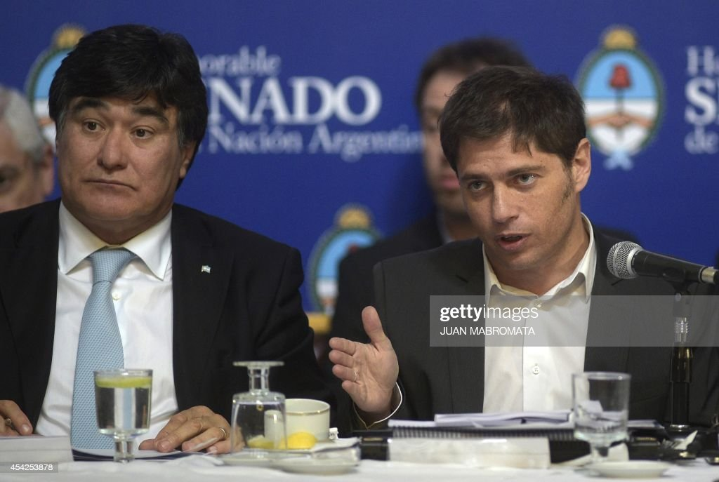 Argentina's Economy Minister Axel Kicillof (R) talks to legislators while debating at the Congress the bill to pay the debt at the Banco Nacion Fideicomiso next to Argentina's Presidency Secretary General Carlos Zannini, in Buenos Aires on August 27, 2014.