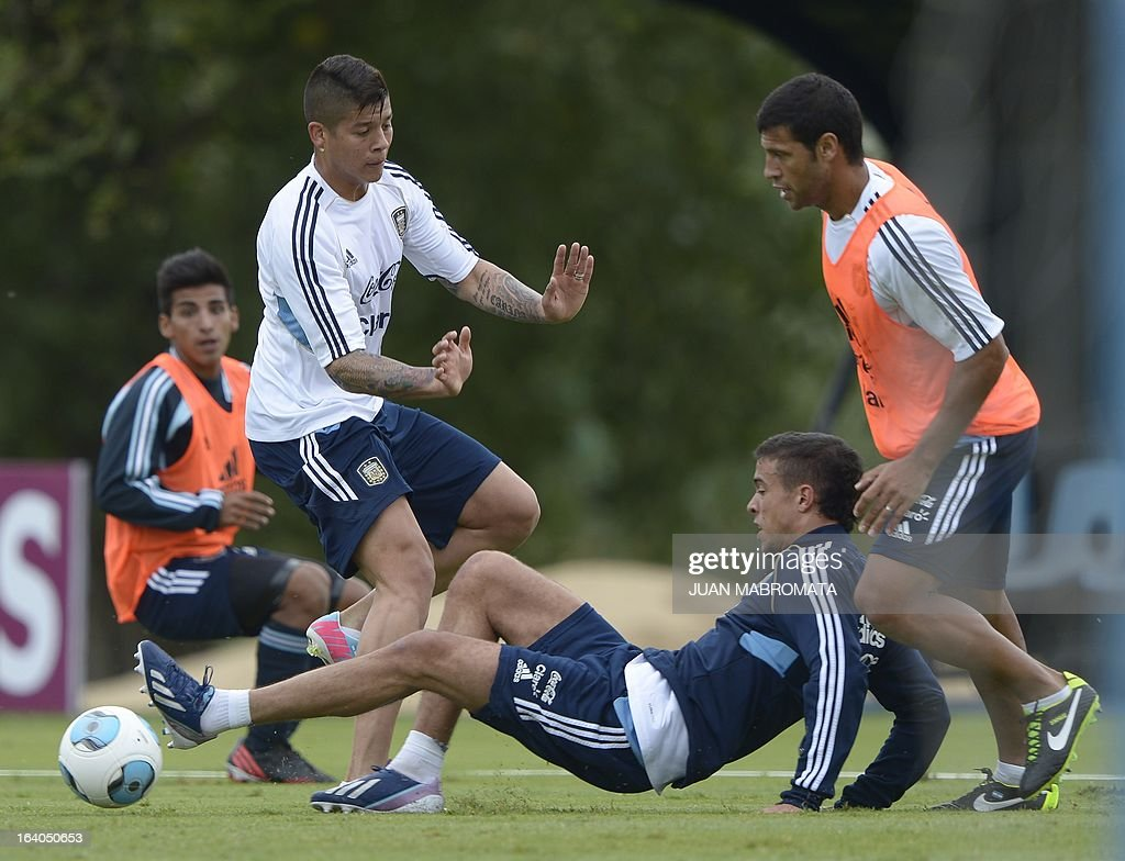 Argentina's footballers defender Marcos Rojo (L) forward Franco Di Santo (C) and defender Sebastian Dominguez vie for the ball during a training session in Ezeiza, Buenos Aires on March 19, 2013 ahead of the Brazil 2014 FIFA World Cup South American qualifier football match against Venezuela on March 22. AFP PHOTO / Juan Mabromata