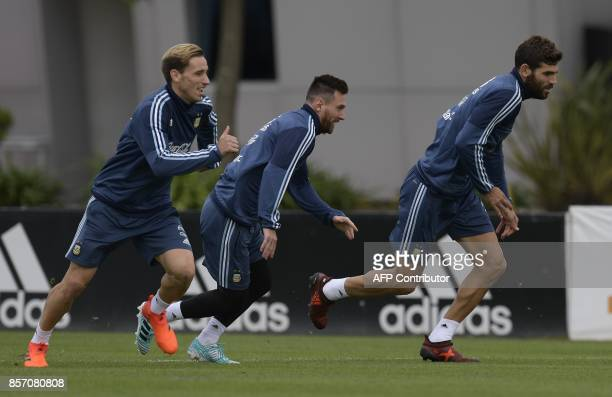 Argentina's footballers Lucas Biglia Lionel Messi and Federico Fazio take part in a training session in Ezeiza Buenos Aires on October 3 2017 ahead...