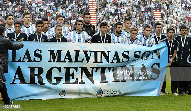 Argentina's footballers pose for photographers holding a banner reading 'The Malvinas / Falkland Islands are Argentine' before a friendly football...