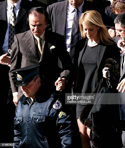 Argentina's former president Carlos Menem and his his wife Cecilia Bolocco are escorted by a policeman from court 07 June 2001 in Buenos Aires Menem...
