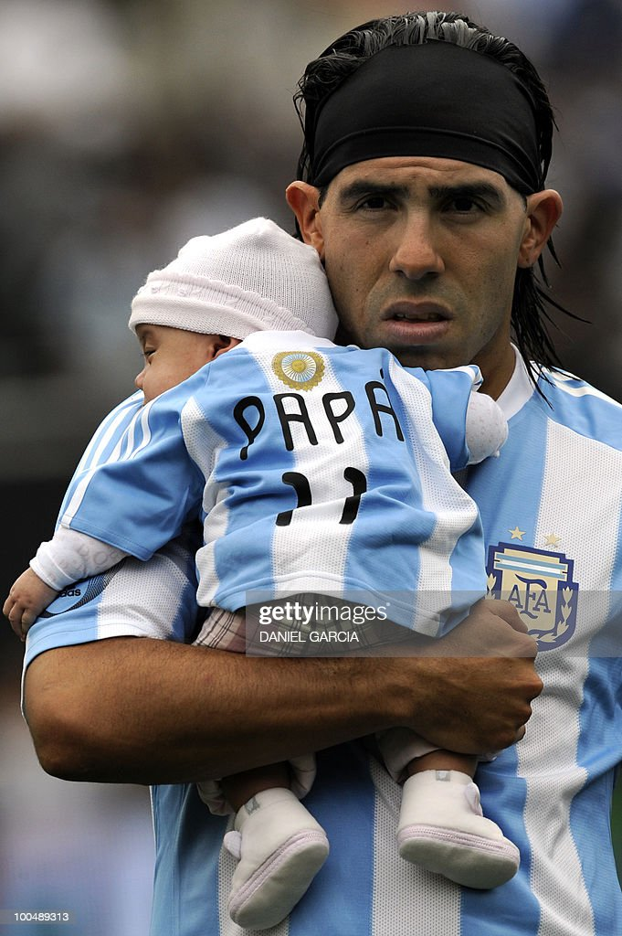 Argentina's forward Carlos Tevez carries one of his daughters in his arms before a friendly football match against Canada at the Monumental stadium in Buenos Aires, on May 24, 2010. Argentina is flying to South Africa for the World Cup finals on Friday, and will play their first match against Nigeria on June 12 in Johannesburg. AFP PHOTO/Daniel GARCIA