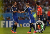 Argentina's forward Gonzalo Higuain shakes hands with Argentina's forward Rodrigo Palacio as he goes off for substitution during the 2014 FIFA World...
