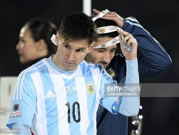 Argentina's forward Lionel Messi and defender Milton Casco take off the second place medal of the 2015 Copa America football championship in Santiago...