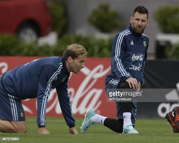 Argentina's forward Lionel Messi and midfielder Lucas Biglia stretch during a training session in Ezeiza Buenos Aires on October 3 2017 ahead of...