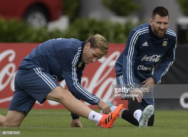 Argentina's forward Lionel Messi and midfielder Lucas Biglia stretch during a training session in Ezeiza Buenos Aires on October 3 2017 ahead of a...