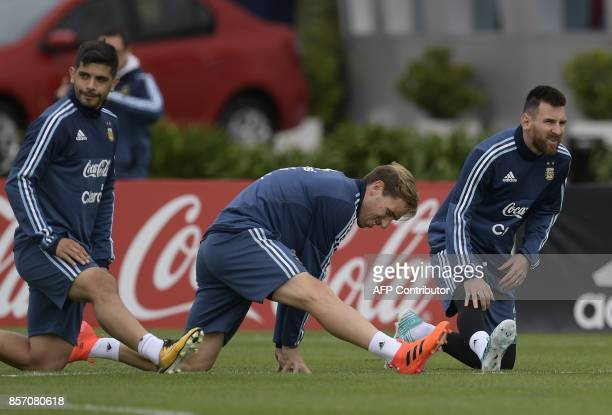 Argentina's forward Lionel Messi and midfielders Lucas Biglia and Ever Banega stretch during a training session in Ezeiza Buenos Aires on October 3...