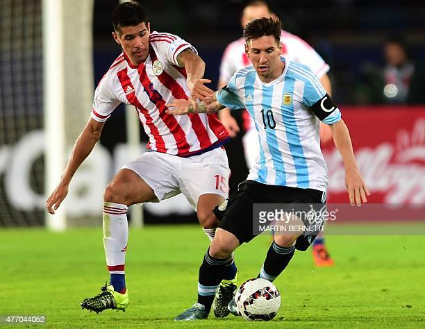 Argentina's forward Lionel Messi and Paraguay's midfielder Victor Caceres vie for the ball during their 2015 Copa America football championship match...